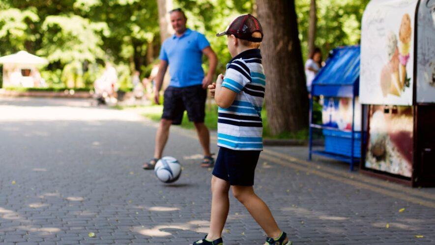 Dreng og mand spiller fodbold